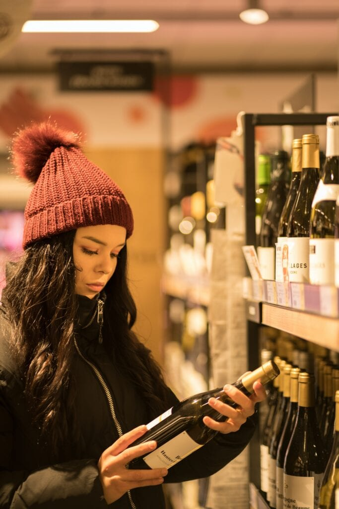 Student with wine in shop