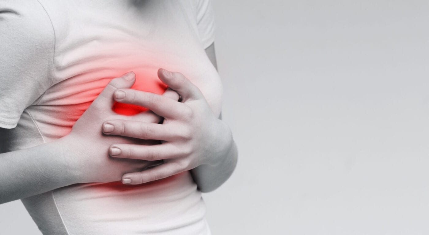 Breast pain. Woman suffering from painful feelings, clutching her boob, monochrome photo with red spot, panorama